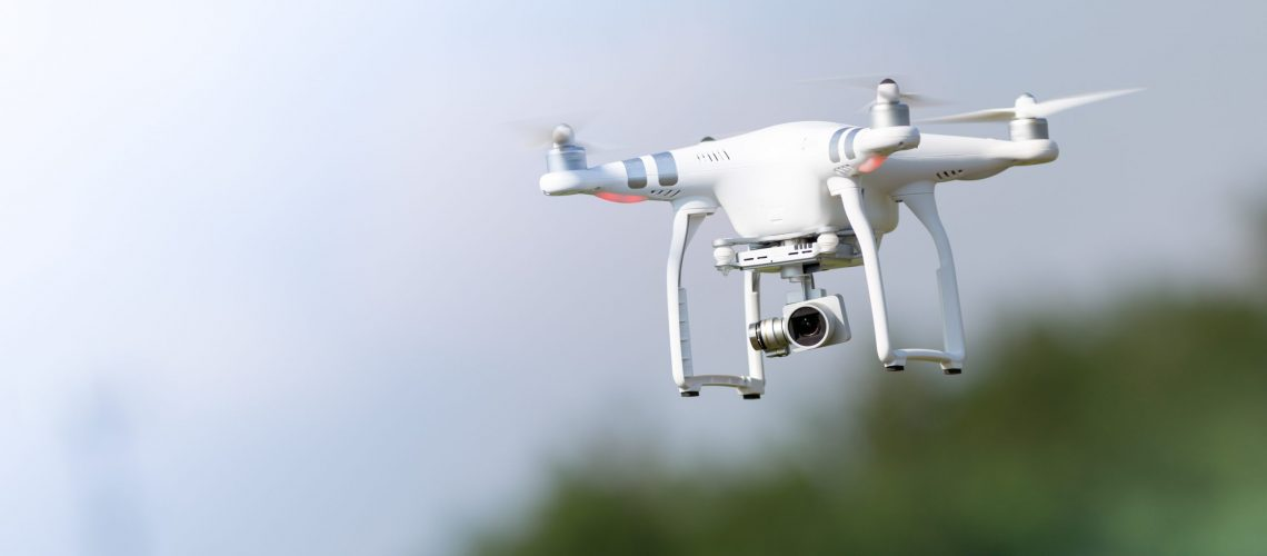 Flying drone in action; photographed on a defocused background. Royalty free image, no logos in the photo.