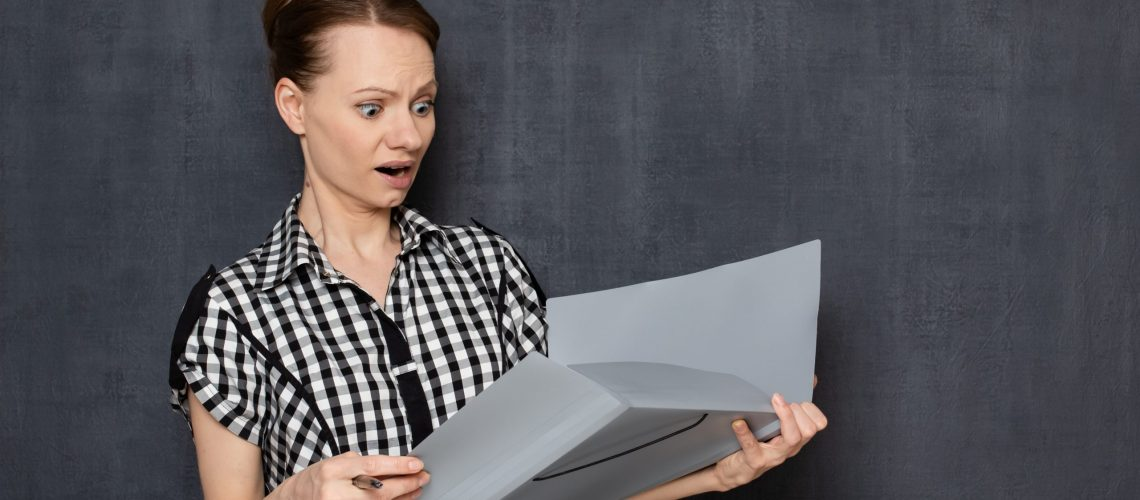 Studio half-length portrait of shocked frightened surprised caucasian girl wearing checkered shirt, looking with indignation and bewilderment at papers in opened folder, standing over gray background