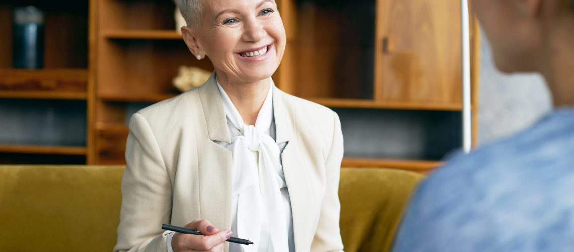 Positive charming middle aged blonde woman recruiter making notes, asking questions about work experience while conducting job interview with female applicant who is sitting with back to camera
